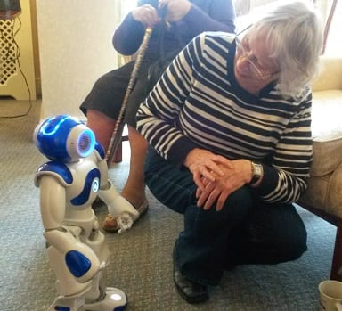 Resident, Kathleen Lockyer interacting with one of the human robots