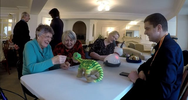 (L-R): Resident, Madge Jones; resident, Anne Hendry; Development Manager, Deborah Hubbard interacting with the animal companion robots.
